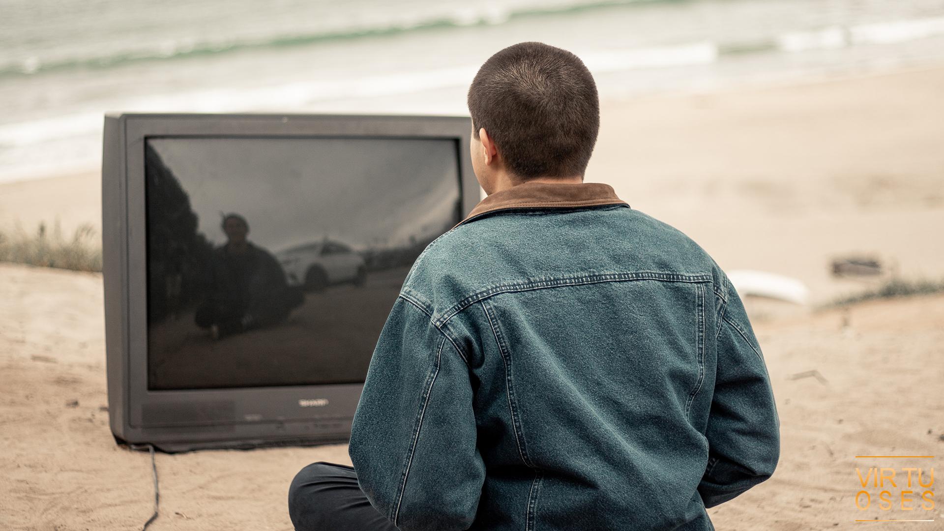 un homme regarde une télé éteint dehors